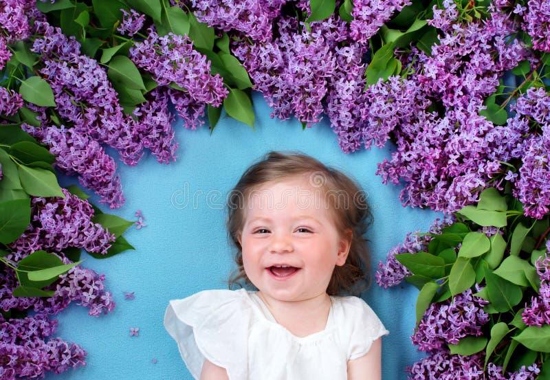 Menina bonita que encontra-se no fundo azul com flores lilás fotos de stock royalty free