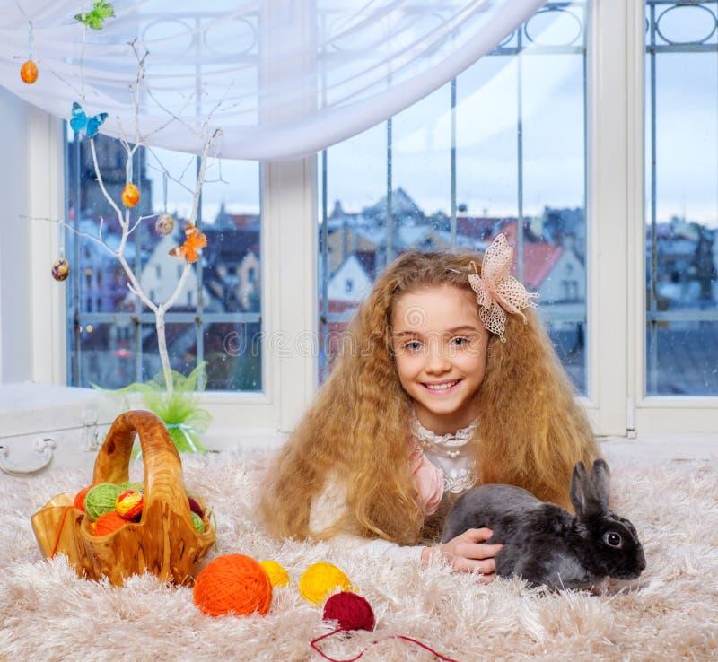 Menina bonita que encontra-se no tapete e que joga com coelho fotos de stock