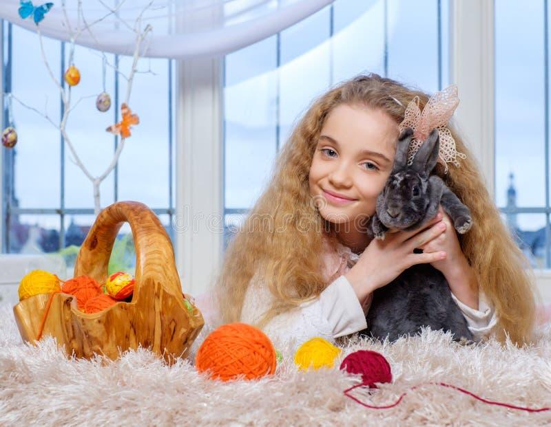 Menina bonita que encontra-se no tapete e que joga com coelho imagens de stock royalty free