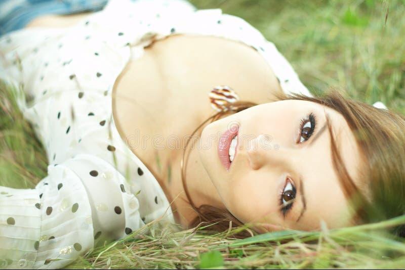 Menina bonita que encontra-se para baixo da grama imagem de stock
