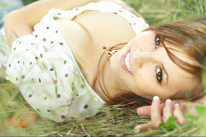 Menina bonita que encontra-se para baixo da grama fotografia de stock royalty free