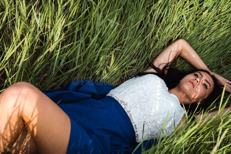 Menina bonita que encontra-se para baixo na grama imagens de stock