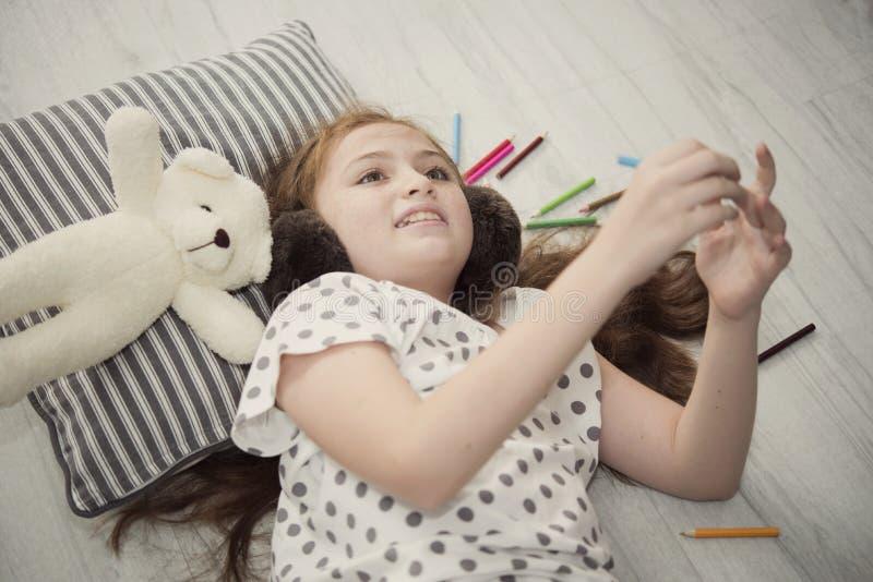 A menina bonita que encontra-se para baixo sorriso relaxa e escuta música foto de stock royalty free