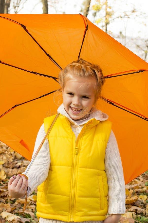 Menina bonita que esconde sob um guarda-chuva fotos de stock