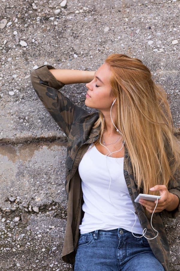 Menina bonita que escuta a música fora imagens de stock royalty free