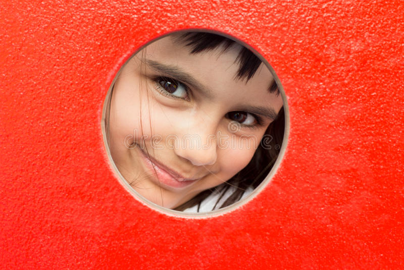 Menina bonita que espreita através de um furo fotografia de stock