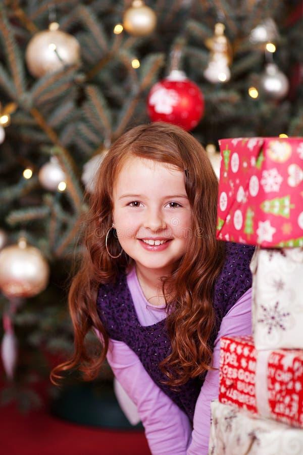 Menina bonita que espreita em torno dos presentes de Natal foto de stock royalty free