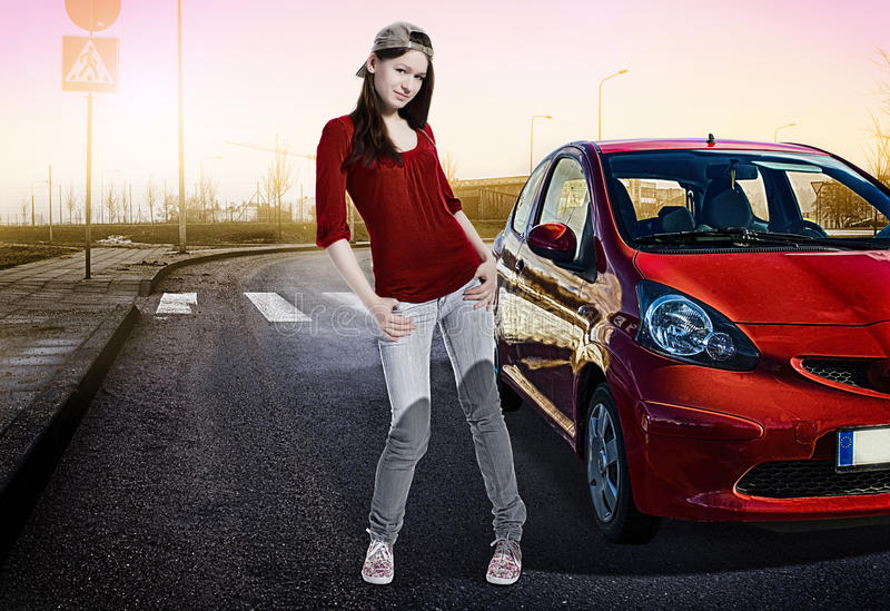 Menina bonita que está ao lado de seu primeiro carro fora na estrada fotos de stock