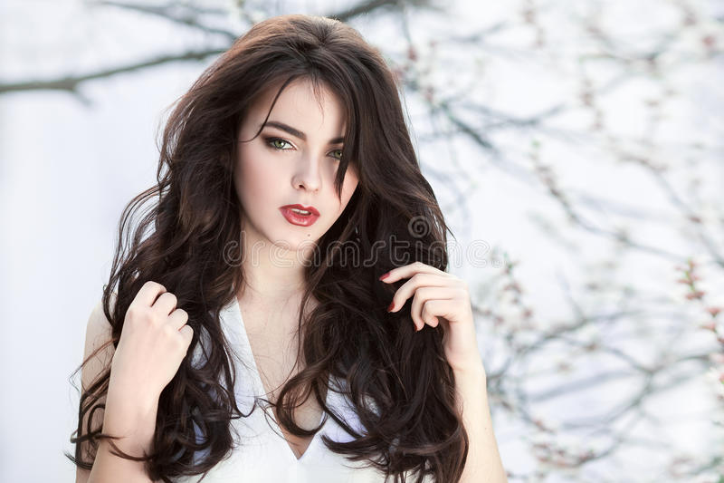 Menina bonita que está na árvore de florescência no jardim sobre o fundo branco imagem de stock royalty free