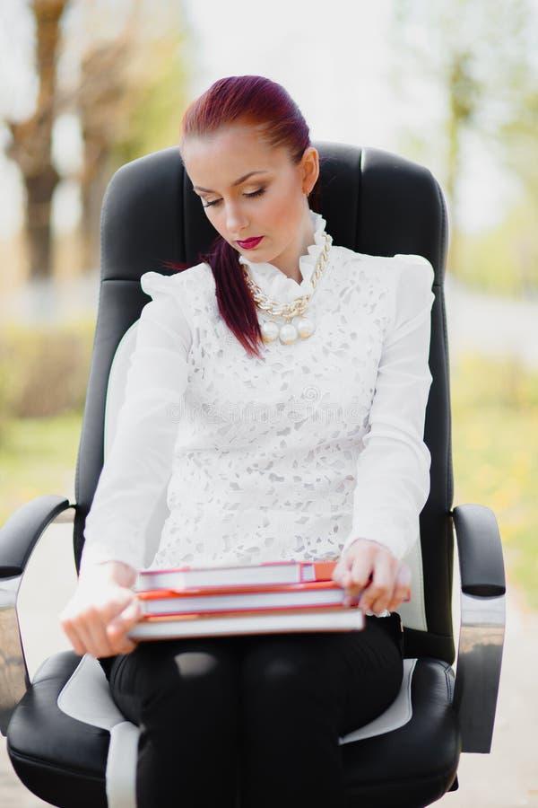 Menina bonita que está na cadeira foto de stock royalty free
