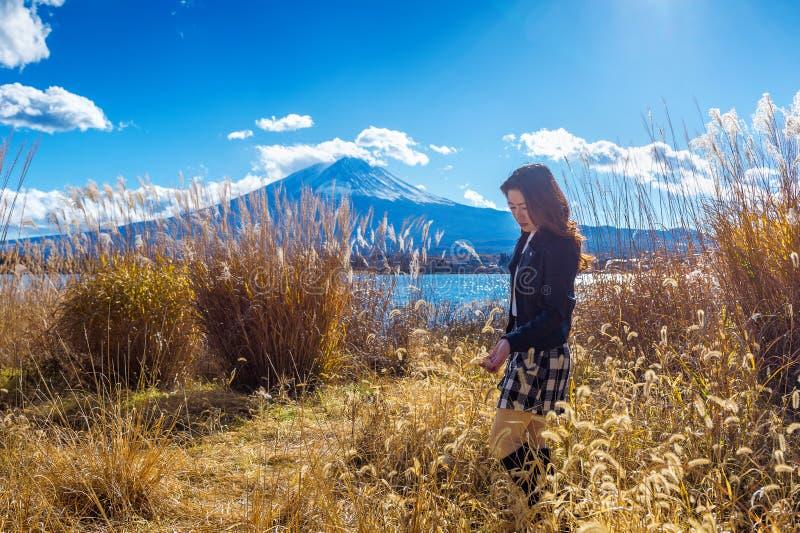 Menina bonita que está no lago do kawaguchiko com vista da montanha de Fuji, outono em Japão foto de stock royalty free