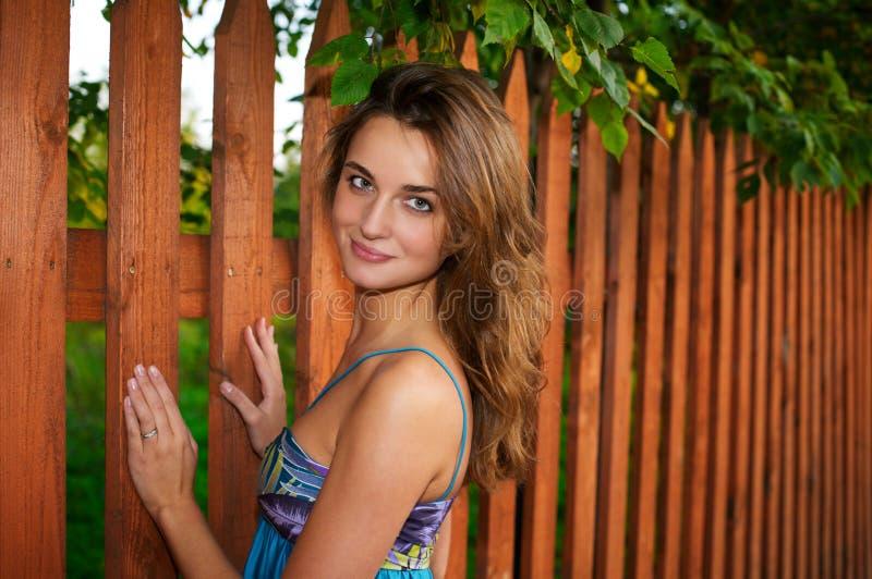 Menina bonita que está perto da cerca foto de stock royalty free
