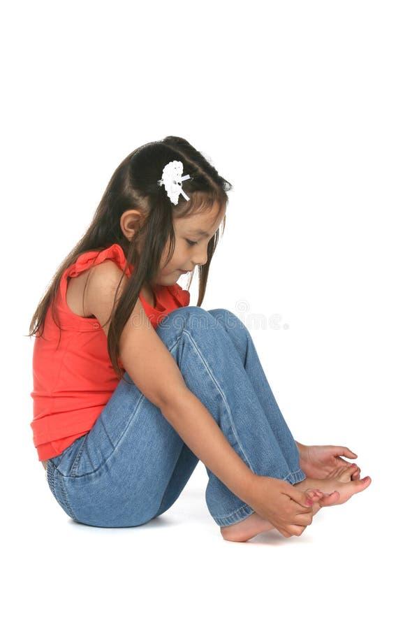 Menina bonita que estuda seus dedos do pé desencapados fotos de stock royalty free