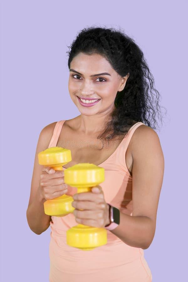 Menina bonita que exercita seu bíceps com pesos foto de stock royalty free