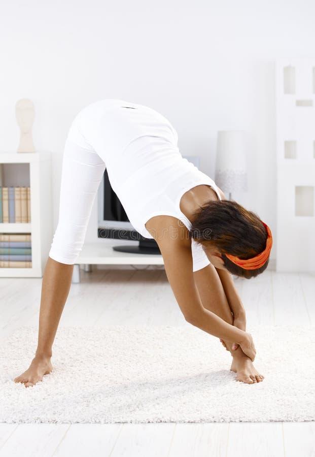 Menina bonita que faz exercícios em casa fotos de stock royalty free