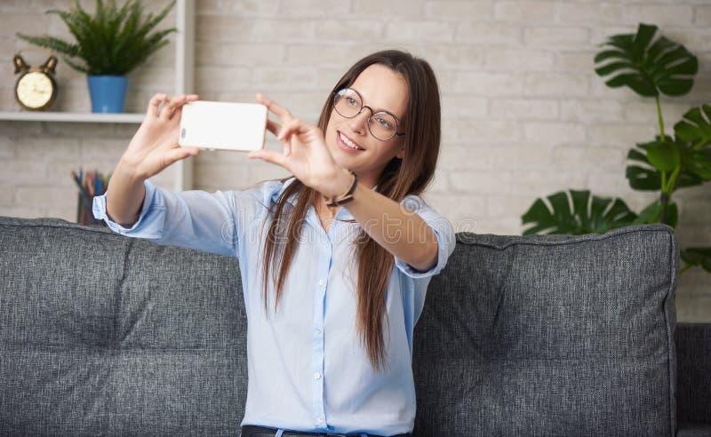 Menina bonita que faz o selfie ao sentar-se em um sofá imagem de stock