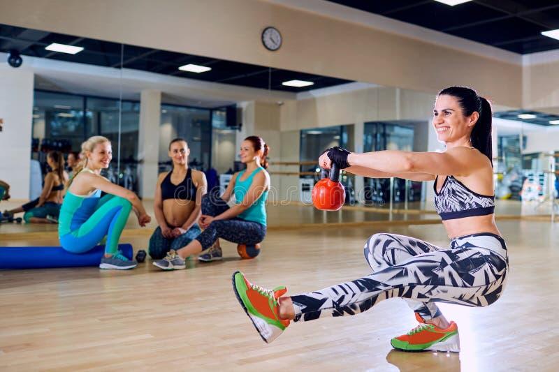 Menina bonita que faz sentar-UPS em um pé no gym fotografia de stock