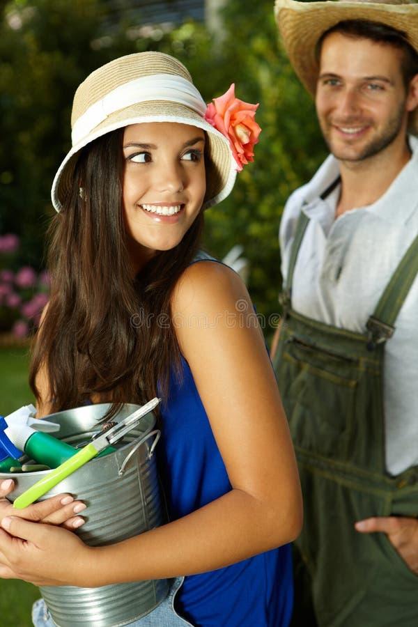 Menina bonita que guarda ferramentas de jardinagem foto de stock
