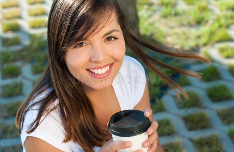 Menina bonita que guarda o café fora no parque e no sorriso fotografia de stock royalty free