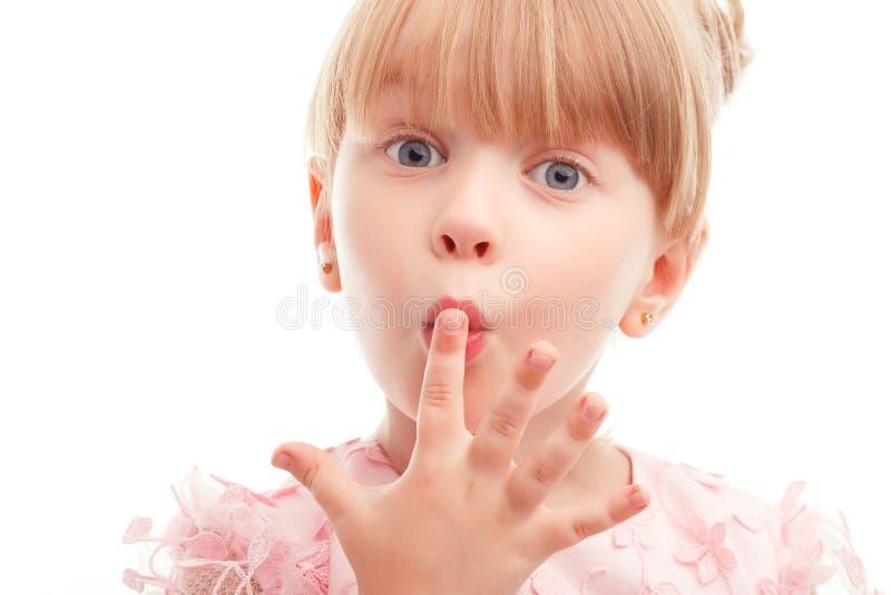 Menina bonita que guarda o dedo em seus bordos fotografia de stock