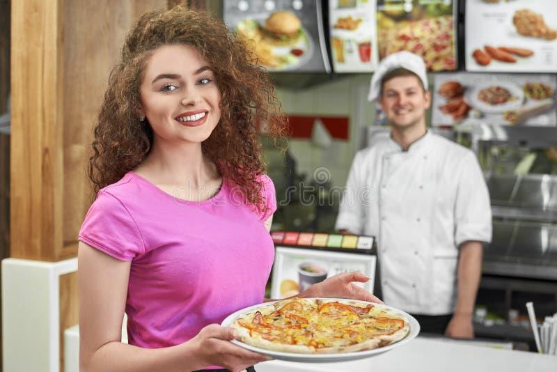 Menina bonita que guarda a pizza deliciosa na pizaria fotos de stock royalty free