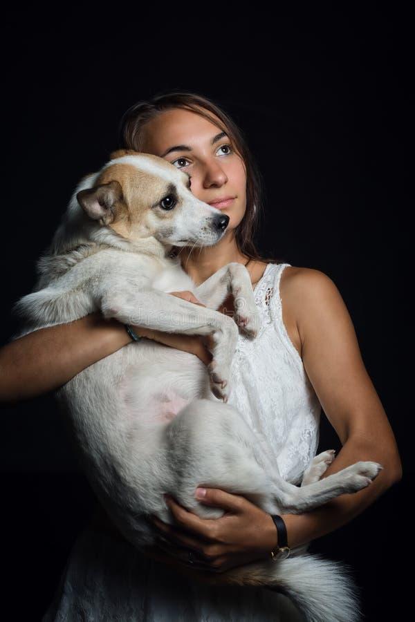 Menina bonita que guarda um cão bonito em seus braços imagem de stock royalty free