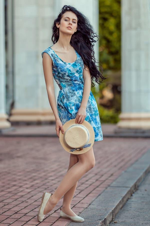 Menina bonita que guarda um chapéu em sua mão imagens de stock royalty free