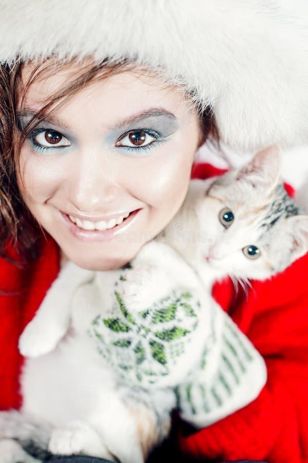Menina bonita que guarda um gatinho pequeno imagens de stock royalty free
