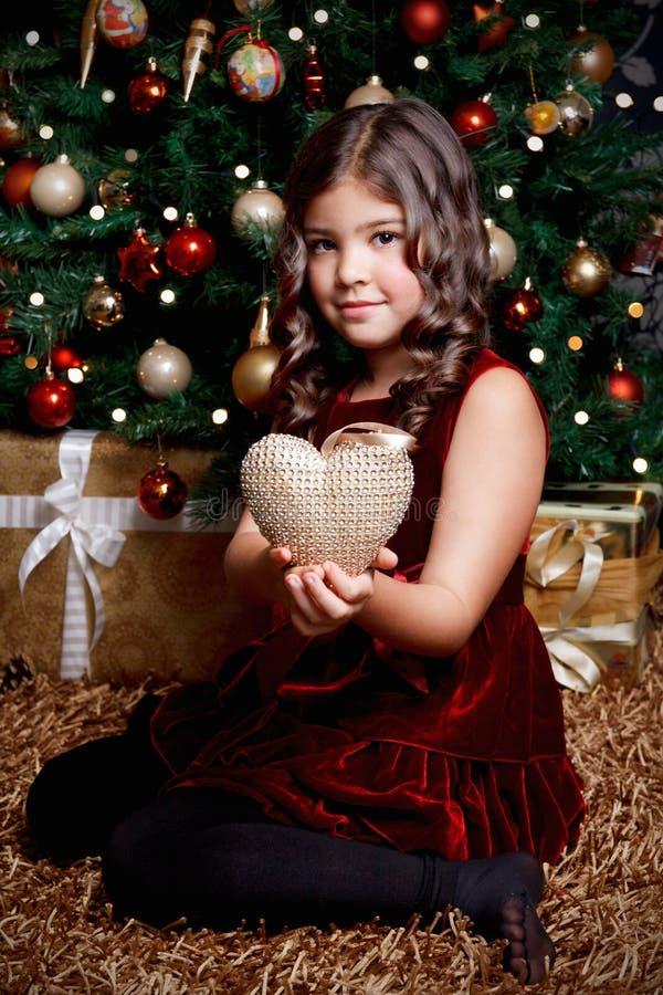 Menina bonita que guarda um ornamento do Natal fotografia de stock