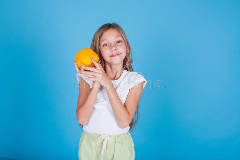 Menina bonita que guarda um vegetal saudável maduro do alimento da pimenta de sino fotos de stock