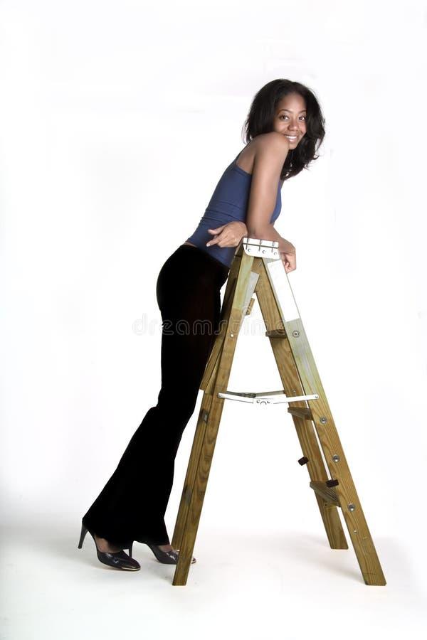 Menina bonita que inclina-se em uma escada fotografia de stock royalty free