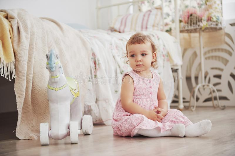 Menina bonita que joga brinquedos Blonde de olhos azuis Cadeira branca Sala do ` s das crianças Retrato pequeno feliz da menina I foto de stock royalty free