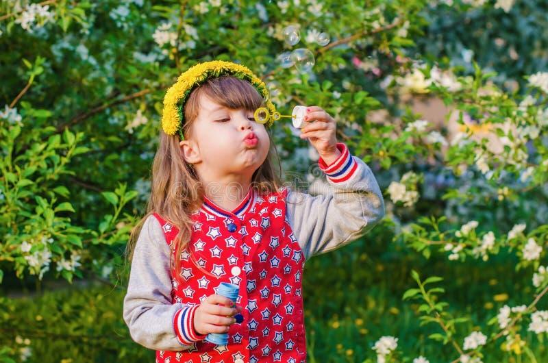 Menina bonita que joga com bolhas de sabão fotografia de stock royalty free