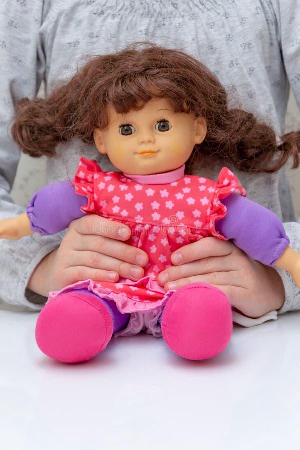 Menina bonita que joga com boneca Boneca bonita no vestido cor-de-rosa imagens de stock royalty free