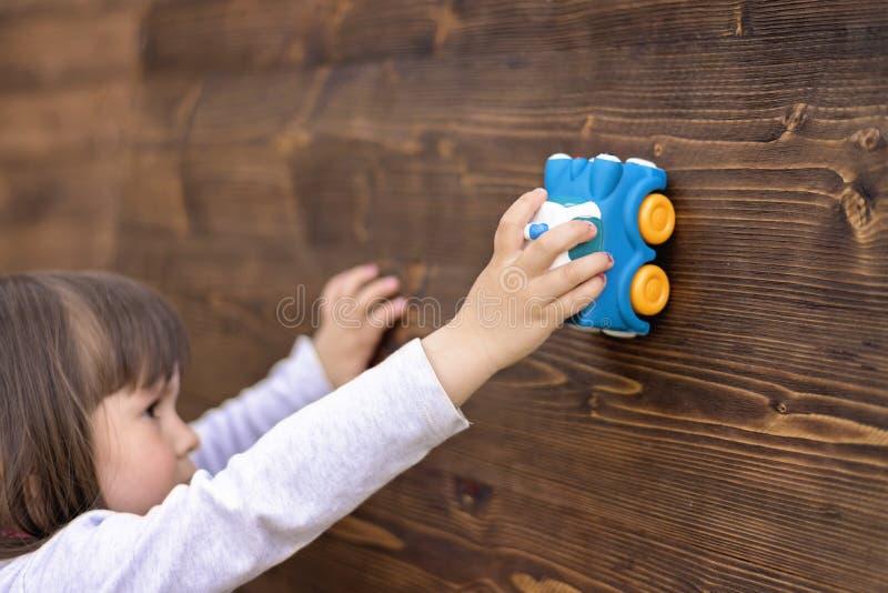 Menina bonita que joga com carro do brinquedo fotografia de stock