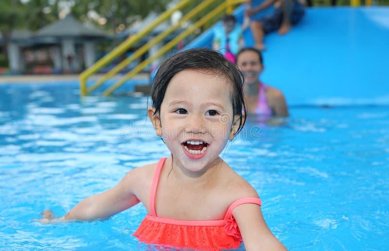Menina bonita que joga na piscina fora fotos de stock