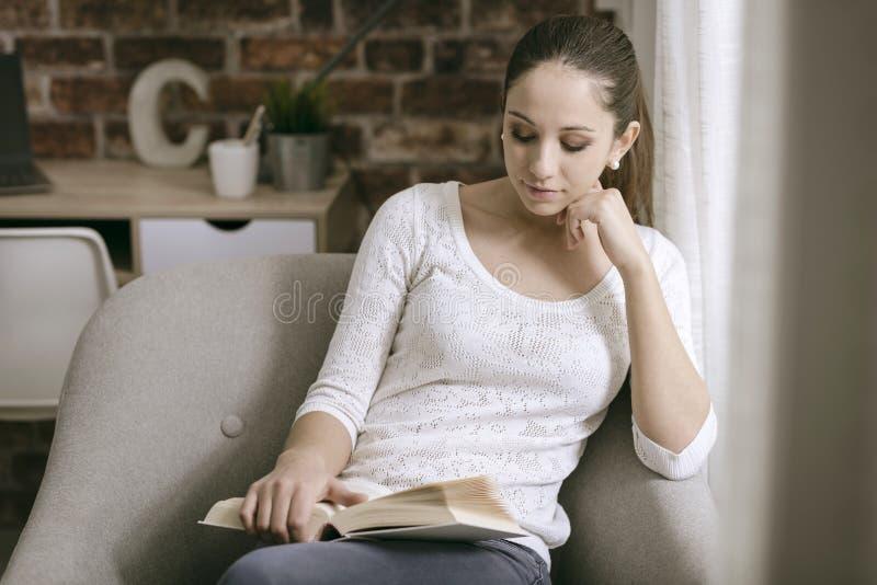 Menina bonita que lê um livro em casa foto de stock royalty free