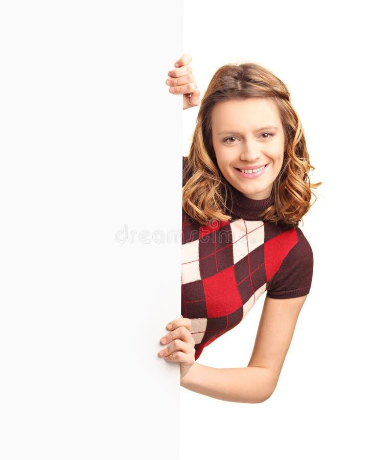 Menina Bonita Que Levanta Atrás De Um Painel Branco Imagem de Stock Royalty Free
