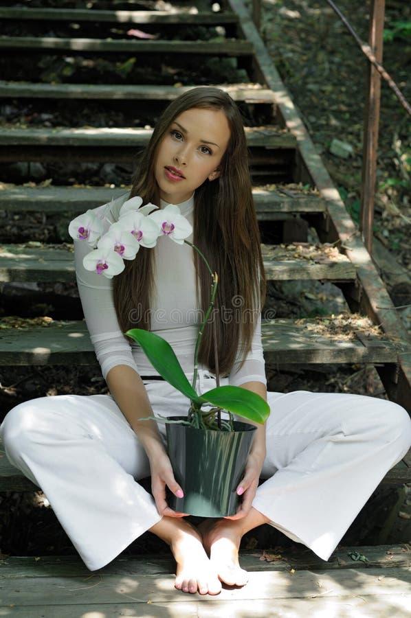 Menina bonita que levanta com flor da orquídea foto de stock