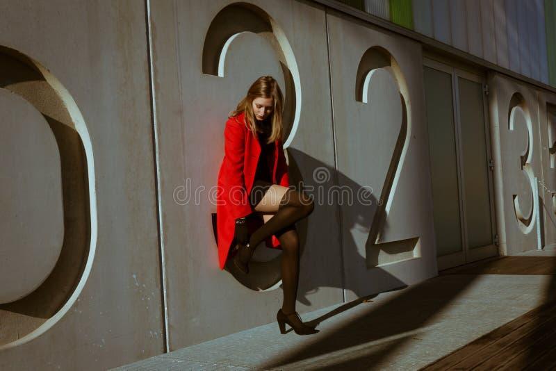 Menina bonita que levanta com revestimento vermelho imagem de stock
