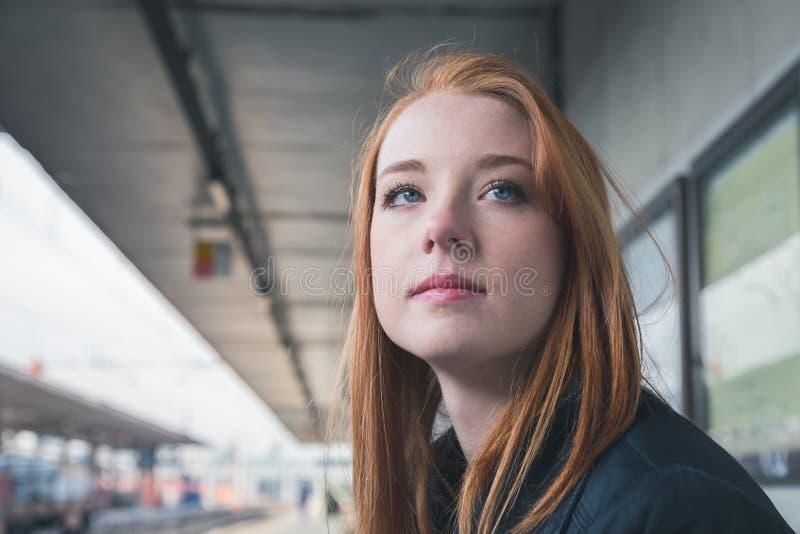 Menina bonita que levanta em uma estação de estrada de ferro foto de stock