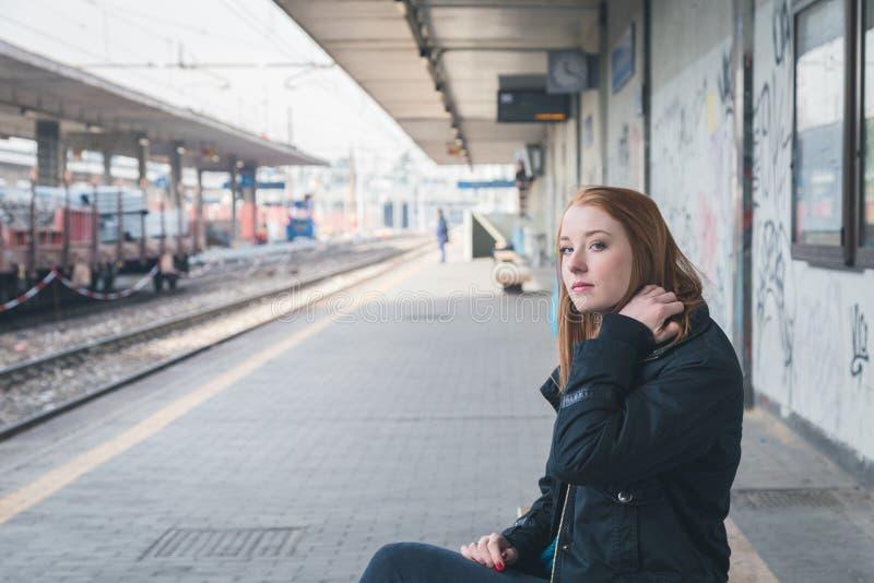 Menina bonita que levanta em uma estação de estrada de ferro fotografia de stock royalty free