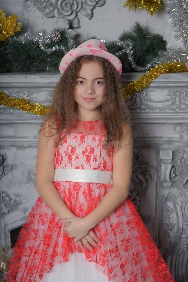 Menina bonita que levanta no vestido vermelho e branco do laço com um chapéu fotos de stock