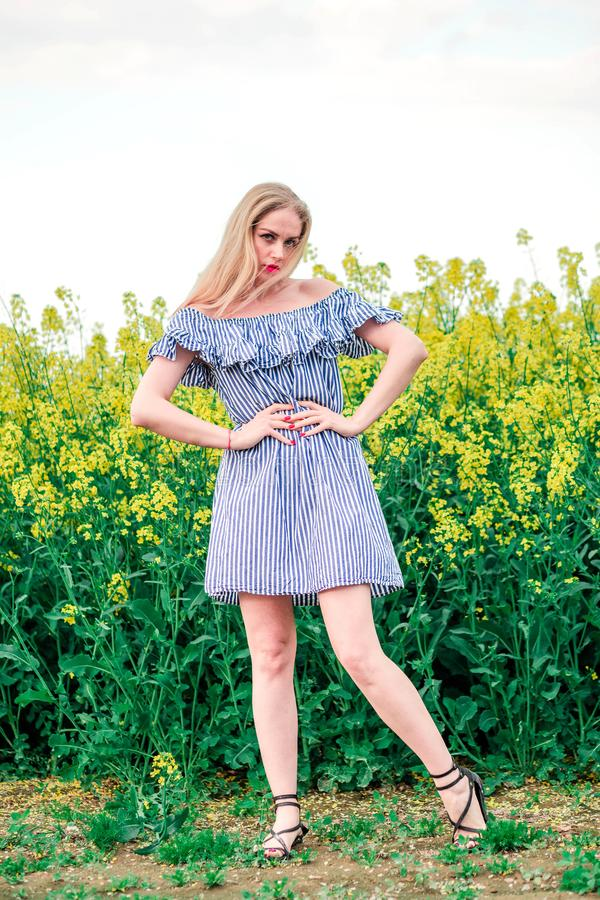 Menina bonita que levanta para a câmera no campo da colza fotografia de stock royalty free