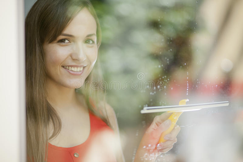 Menina bonita que limpa uma porta de vidro imagens de stock royalty free