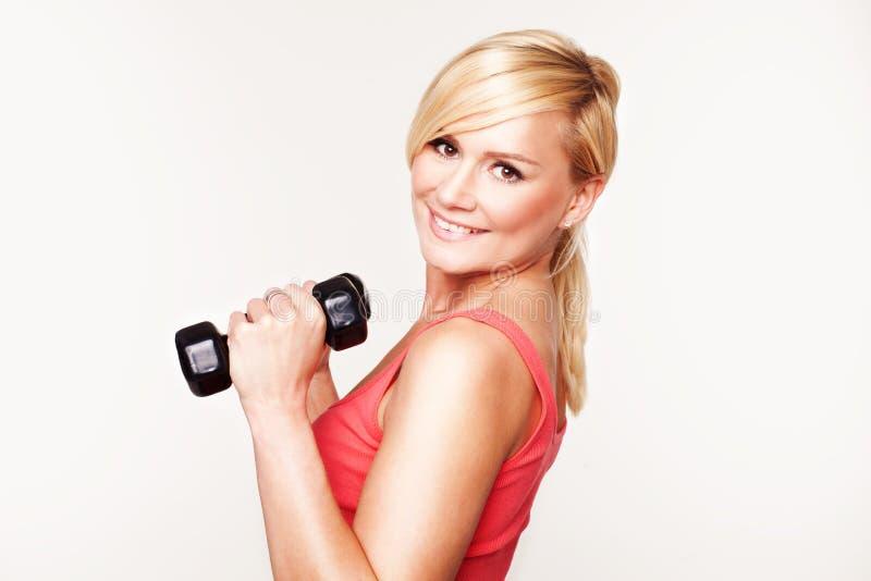 Menina bonita que mantem seu exercício bonito da forma foto de stock