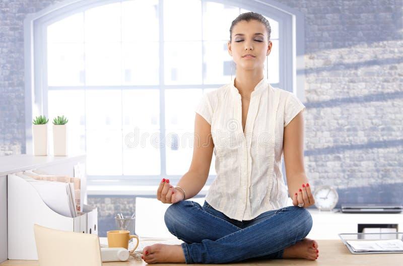 Menina bonita que meditating sobre a mesa imagem de stock royalty free