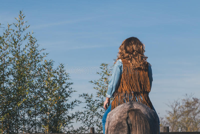 Menina bonita que monta seu cavalo cinzento imagens de stock