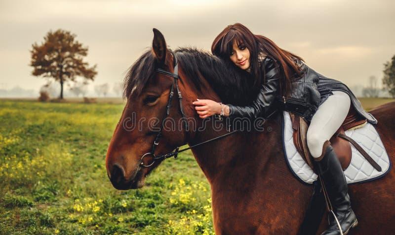Menina bonita que monta um cavalo marrom imagens de stock
