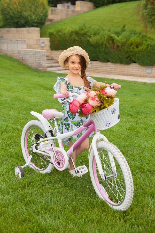 Menina bonita que monta uma bicicleta através do parque Natureza, estilo de vida imagem de stock